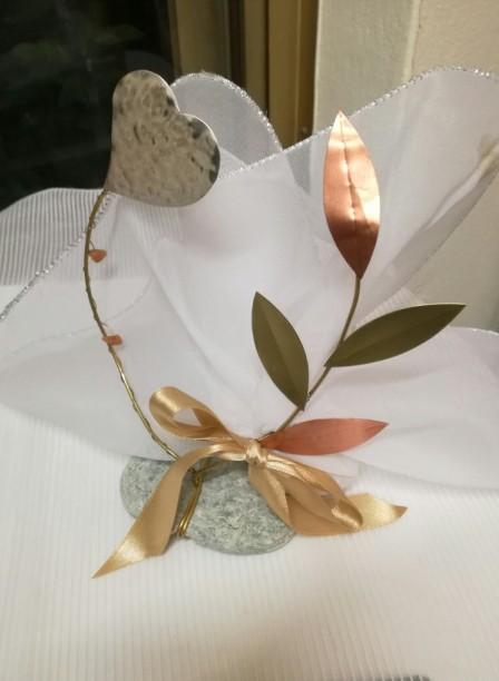 Μπομπονιέρα γάμου ελιά-καρδιά μεταλλικά στοιχεία σε βότσαλο